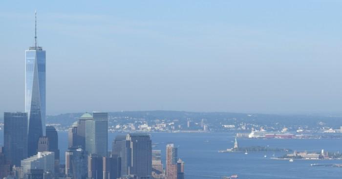 אליס איילנד ופסל החירות (מצד ימין) לנגד מרכז הסחר העולמי החדש ניו יורק