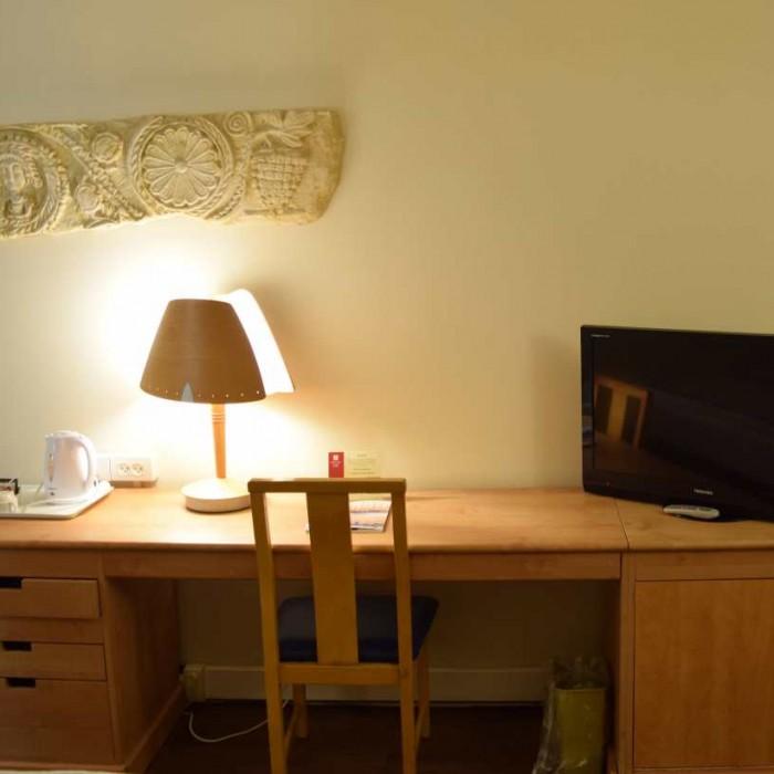 שולחן כתיבה וטלוויזיה בחדר מלון לאונרדו פריוילג' ים המלח